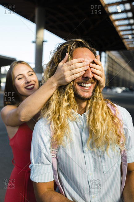 Young woman covering eyes of smiling boyfriend from behind in city