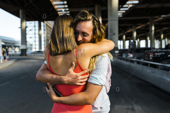 Happy male hipster hugging girlfriend while standing on street in city