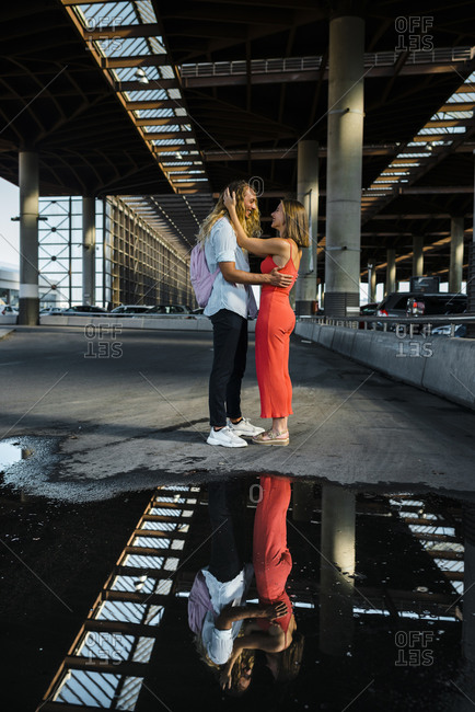 Couple standing face to face by reflection on puddle in city