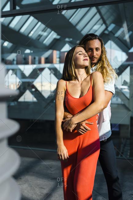 Boyfriend cuddling his girlfriend from behind at railroad station