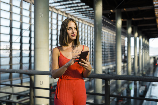 Beautiful young woman looking away while holding smart phone at railroad station