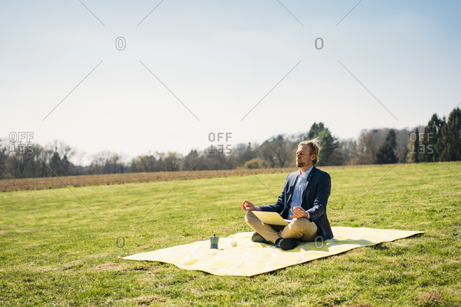 Male entrepreneur sitting with laptop while meditating in lotus position on picnic blanket at park against clear sky
