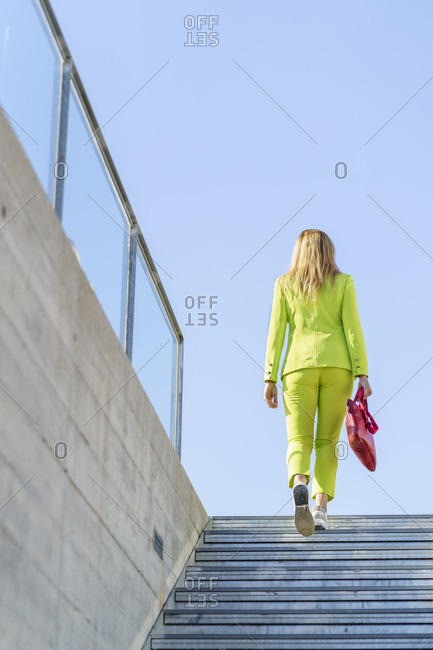 Businesswoman moving on steps against clear sky