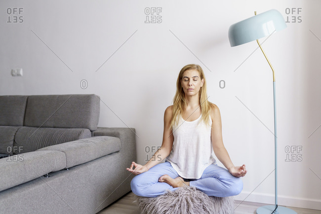 Woman meditating against wall in living room at home