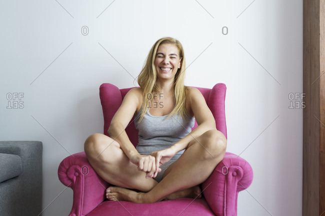 Cheerful mature woman sitting on armchair at home