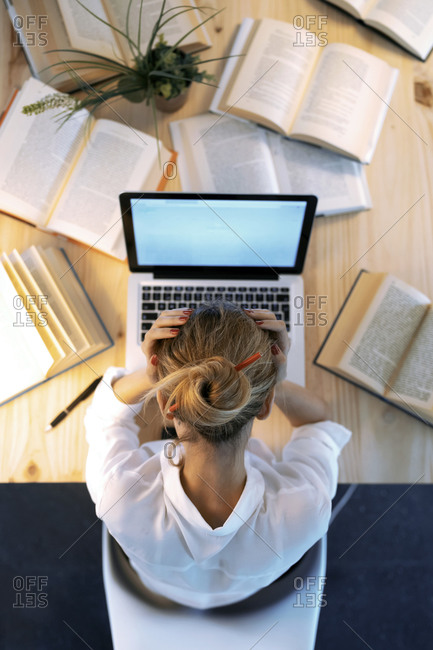 Tired woman with head in hands at home office