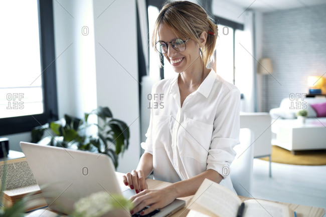 Smiling freelancer working over laptop at home