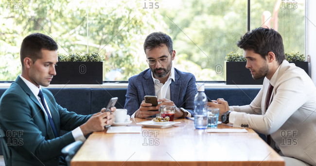 Male business professionals busy in using smart phones during meeting in restaurant