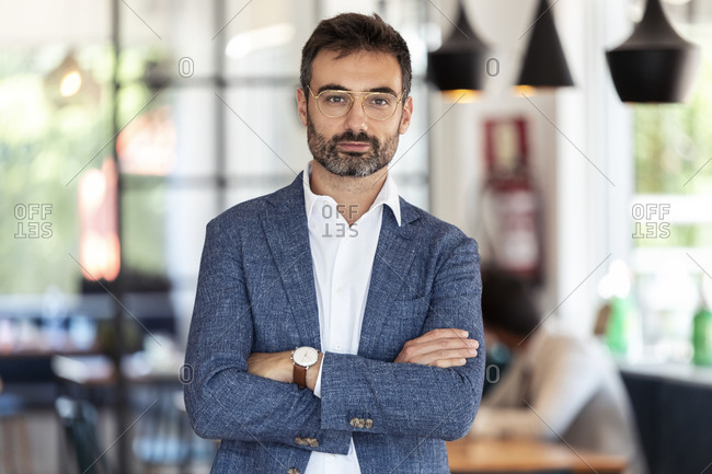 Confident businessman standing with arms crossed in restaurant
