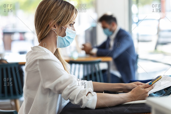 Thoughtful young woman wearing protective mask while sitting in cafe during coronavirus outbreak