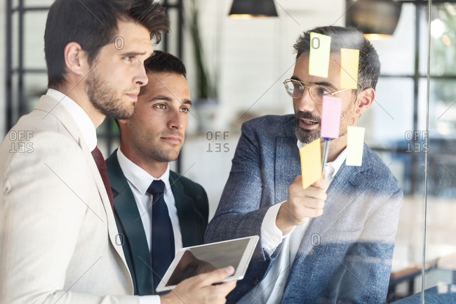 Businessman explaining coworkers over sticky notes during meeting
