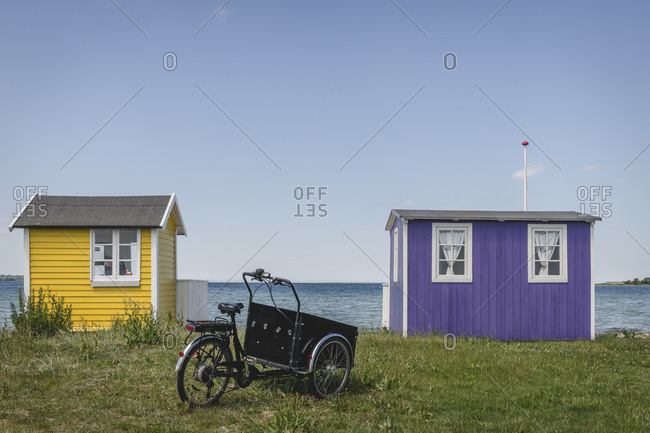 Denmark- Region of Southern Denmark- Aeroskobing- Old-fashioned tricycle standing in front of small coastal bathhouses