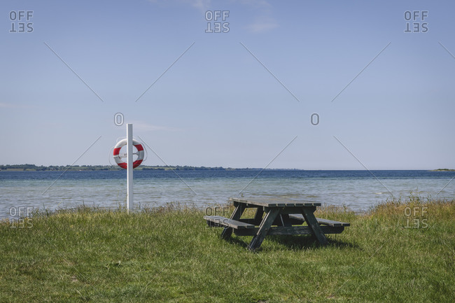 Empty picnic table and pole with life belt