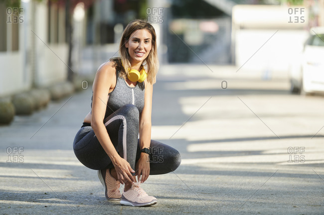 Smiling woman with headphones tying shoelace at sidewalk