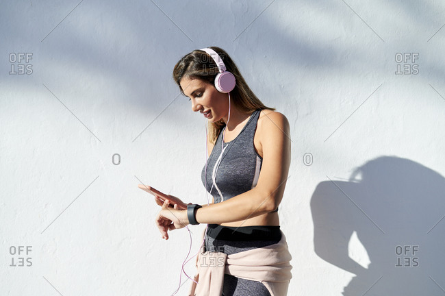 Smiling woman with headphones using phone while checking the time in city
