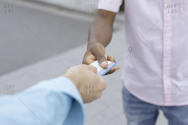 Friend giving credit card to man in city
