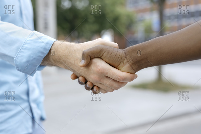 Friends shaking hands in city