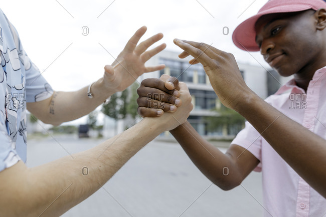 Smiling man bonding with male friend in city