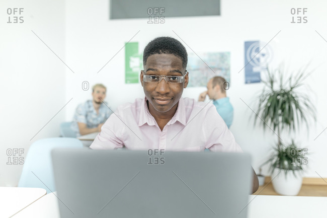 Business person working on laptop while colleagues sitting in background at workplace