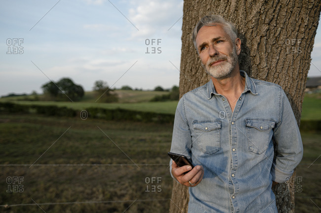 Mature man with smartphone leaning against a tree trunk in the countryside