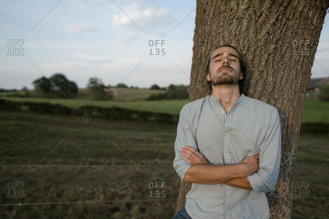 Relaxed young man leaning against a tree trunk in the countryside