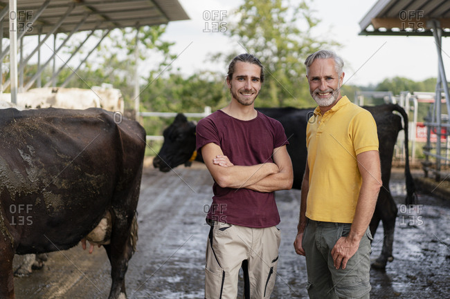 Portrait of smiling mature farmer with adult son at cow house on a farm