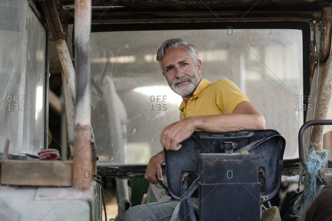 Portrait of a mature farmer on a tractor