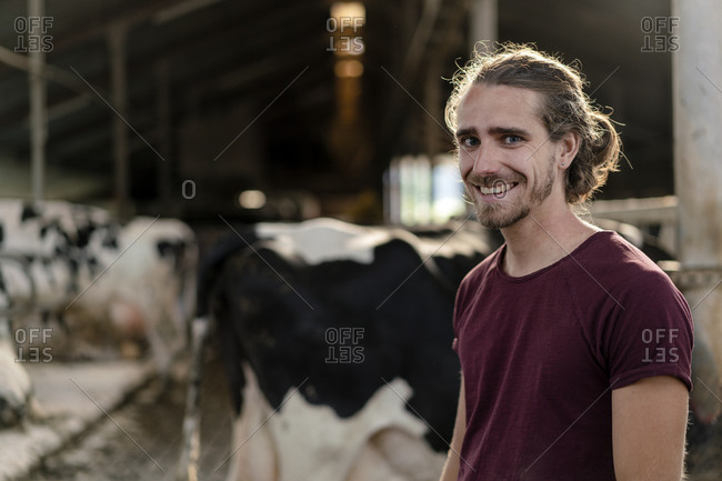 Portrait of a smiling young farmer at cow house on a farm