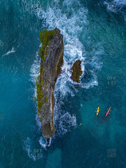 Indonesia- Bali- Aerial view of kayakers passing stack rock near shore of Nusa Penida island