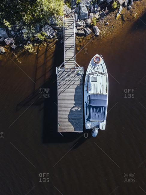 Aerial view of motorboat moored at brown shore of Lake Ladoga