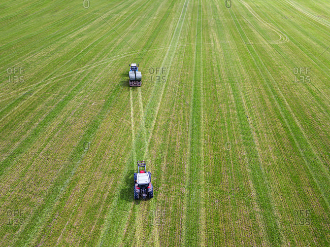 Aerial view of two tractors collecting hay bales in field