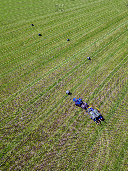 Aerial view of tractor collecting hay bales in field