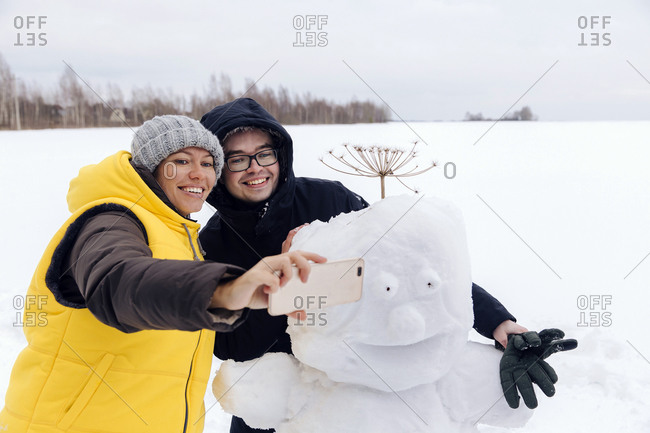 Smiling couple taking selfie with snowman
