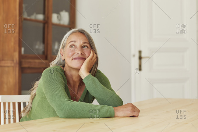 Smiling woman day dreaming while sitting by table at home