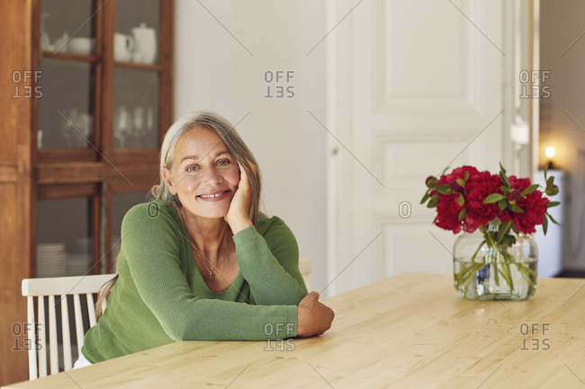 Smiling woman day dreaming by table at home