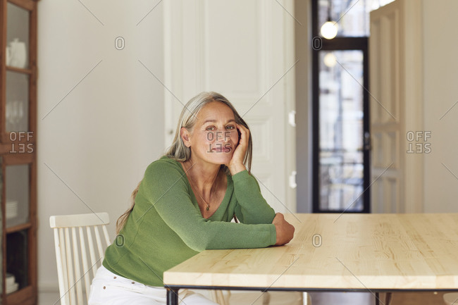 Smiling mature woman day dreaming by table at home