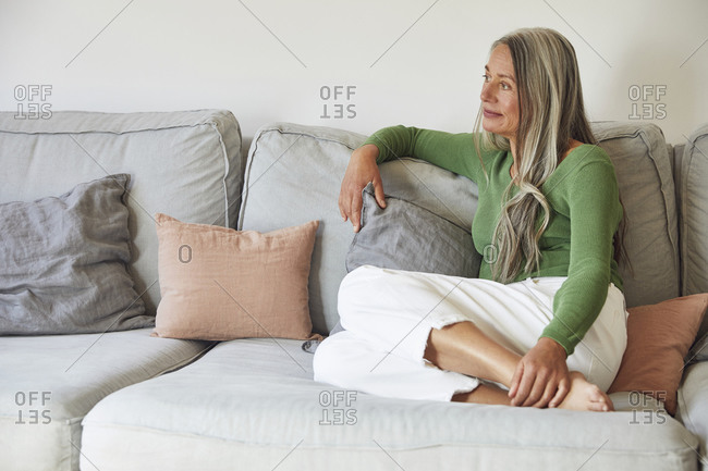 Mature woman day dreaming while sitting on sofa at home