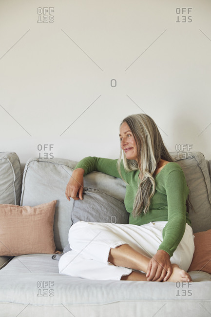 Smiling woman day dreaming while sitting on sofa at home