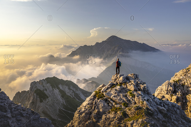 Hiker admiring awesome view while standing on mountain peak at Bergamasque Alps- Italy