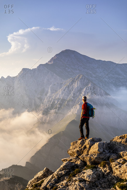 Hiker standing while admiring view of mountain at Bergamasque Alps- Italy