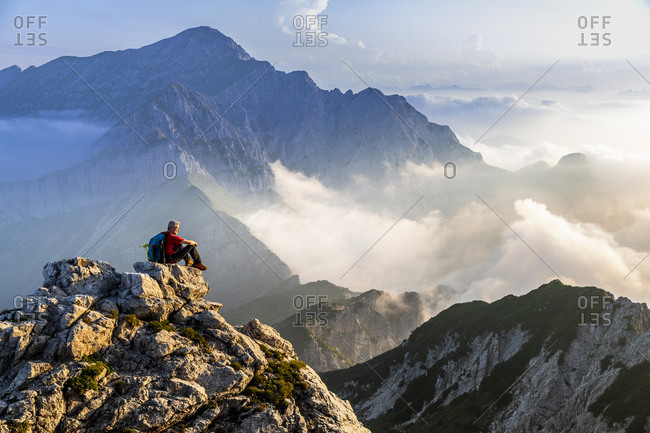 Man sitting and admiring mountain landscape during sunrise at Bergamasque Alps- Italy