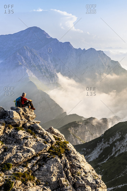 Hiker admiring view while sitting on mountain peak at Bergamasque Alps- Italy