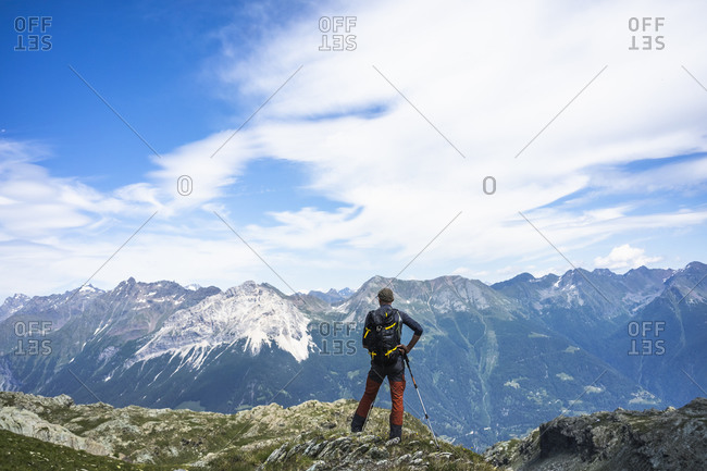 Hiker standing on top of peak while looking at mountains- Western Rhaetian Alps- Sondrio- Italy