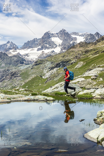 Man walking by lake with reflection at Western Rhaetian Alps Sondrio- Italy