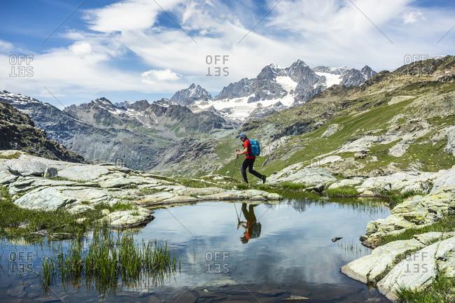 Man exploring while walking by lake at Western Rhaetian Alps- Sondrio- Italy