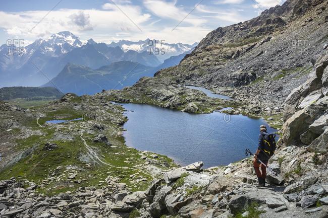 Man hiking by lake at Western Rhaetian Alps- Sondrio- Italy