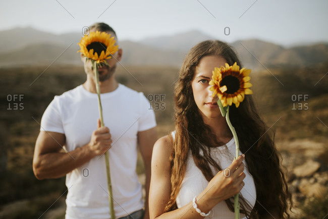 Woman and man hiding face with sunflowers during sunset