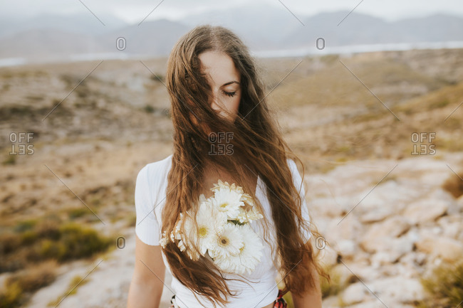Beautiful woman with flowers in field