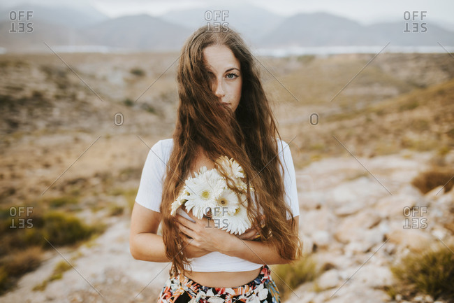 Beautiful woman with flowers standing in field