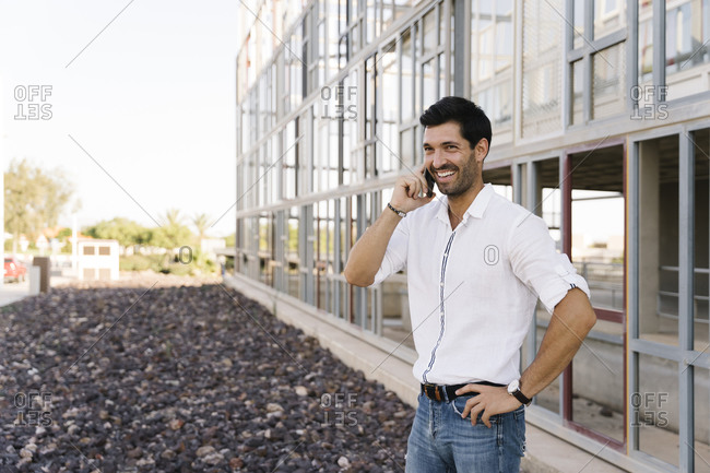 Smiling businessman talking on phone outside building